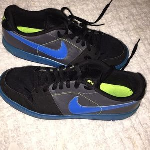 Black, blue and neon green Nike tennis shoes.